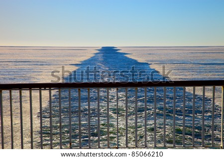 Wake in the frozen sea as seen from the stern of the ship. - stock photo