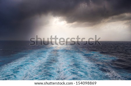 wake of water seen from behind the boat on a stormy night - stock photo