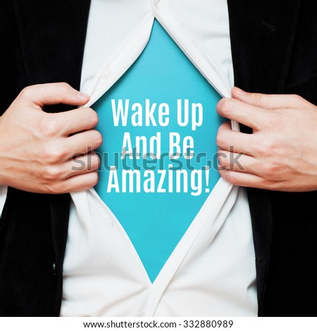 Wake Up And Be Amazing ! Man showing a superhero suit underneath his shirt with a message text written on it. - stock photo