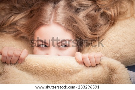 Wake up. Lovely young woman waking up happily after good night sleep, smiling girl in the morning in bed covering her face under blanket - stock photo