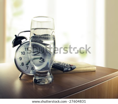 Wake up with the alarm clock and a glass of water - stock photo