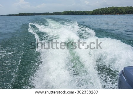 wake waves from boat on lake - stock photo