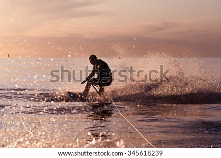 Wakeboard ride on tranquil waters at a sunset. Water splashing from the tow boat to a rookie wake boarder loosing balance - stock photo