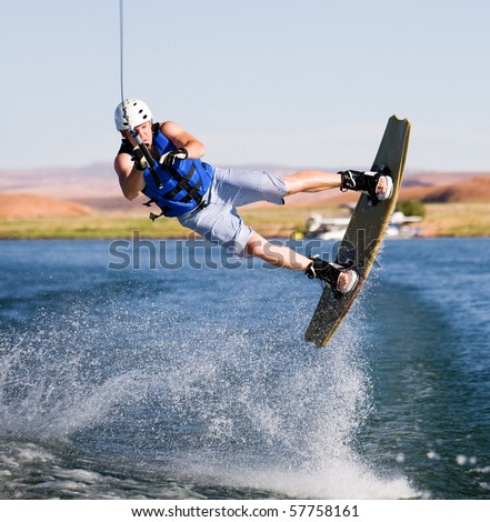 Wakeboarder boarding behind a boat with beautiful Lake Powell in the background at Glen Canyon National Recreation Area, Utah, USA - stock photo