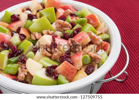Waldorf salad made with granny smith apples, gala apples, walnuts, cranberries, spring onions, and celery in a healthy vinaigrette base.