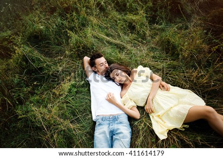Walk a happy young couple on the nature outside the city.