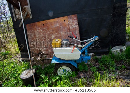 walk-behind tractor standing near a garage in the grass - stock photo
