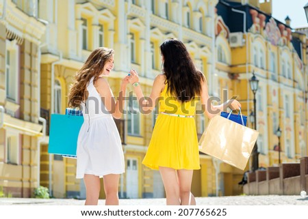 Walk girlfriends shopaholics. Two attractive young girl holding shopping bags  near shop while walking down the street holding hands outdoors - stock photo