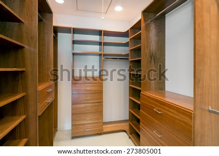 Walk-in closet lined with cherry wood built-ins. Big empty walk in wardrobe in luxurious house. - stock photo