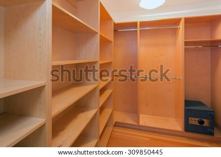 Walk-in closet with wooden built-ins and fireproof combination lock safe. Big empty walk in wardrobe in luxurious house. - stock photo