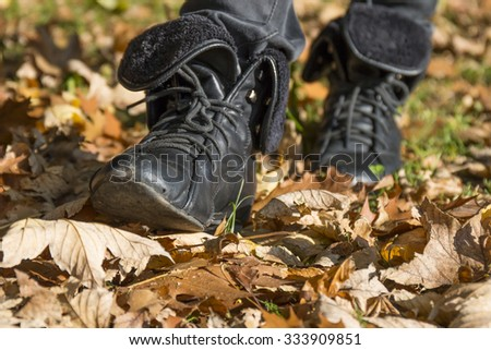 Walk in the autumn park. Legs of a woman wearing boots wade dry autumn leaves