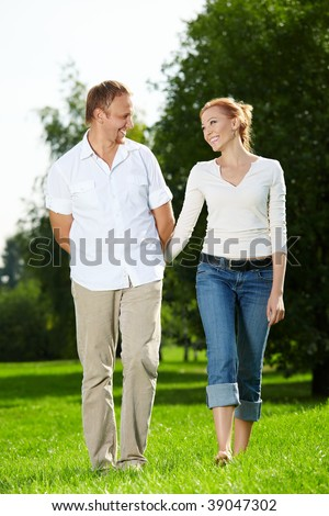 Walk of a cheerful couple in a summer garden