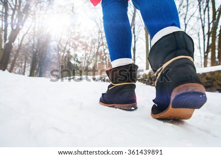 walk of girl in boots on snow - stock photo