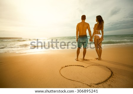 Walk on the beach of loving couple with heart shape on the sand. - stock photo