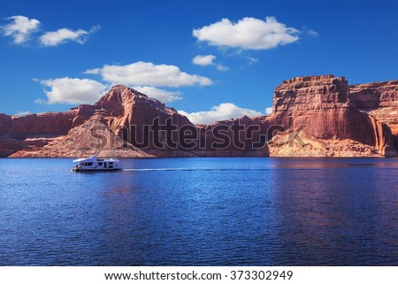 Walk on white boat on a sunny day. Scenic huge artificial water basin of the Colorado River, USA. Lake Powell is surrounded by magnificent sandstone hills - stock photo