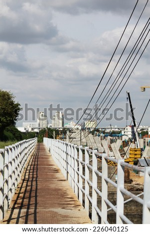 Walk path beside the railway and the under-construction express way. - stock photo