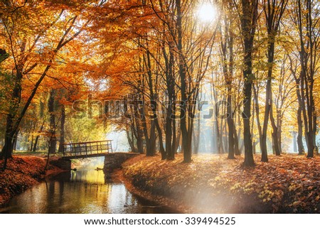 Walk way bridge over river with colorful trees in autumn time - stock photo