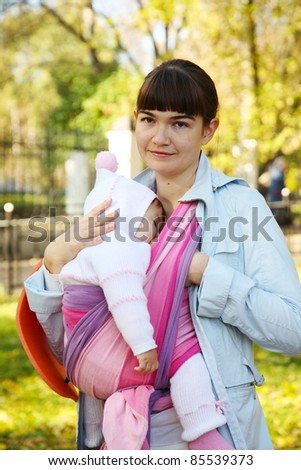 Walk with the child in a baby sling. Breastfeeding - stock photo