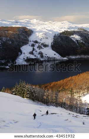 Walkers descending the path towards Thirlmere from Helvellyn in winter in the English Lake District