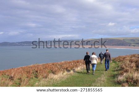 Walkers on Baggy Point with Woolacombe and its Beach in the Background on the Coast of North Devon, England, UK
