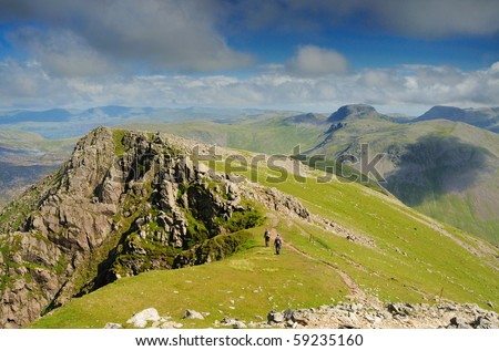 Walkers on Pillar mountain in the English Lake District, with Great Gable in the background - stock photo
