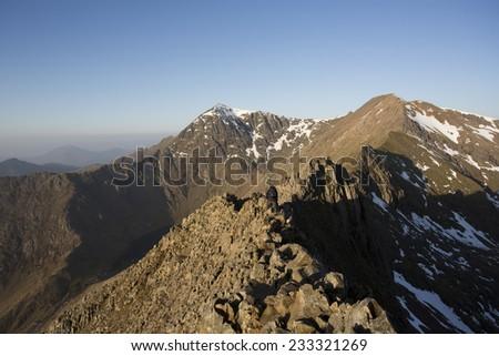 walking along rocky mountain ridge towards snowdon - stock photo