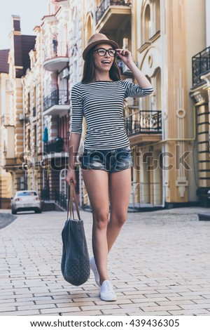 Walking along the street.  Full length of beautiful young woman carrying bag and looking away with smile while walking along the street - stock photo