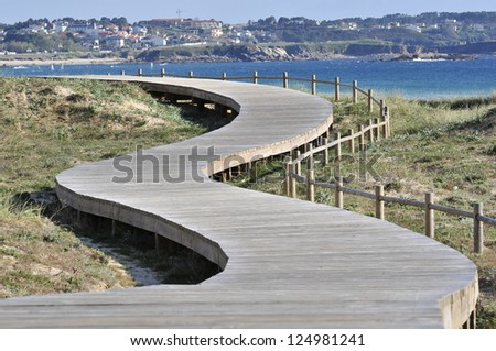 Walking and hiking route parallel to the beach Lanzada in O Grove (Pontevedra). The wooden walkway is supported in the dunes without work to destroy this fragile ecosystem. - stock photo