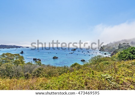 Walking atop the cliff lined streets of Trinidad California, a sleepy, remote, touristic, fishing village, you see fog on the horizon & boats safely anchored, in its protective harbor & safe bay.