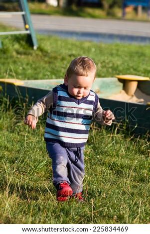 Walking baby on the playground - stock photo