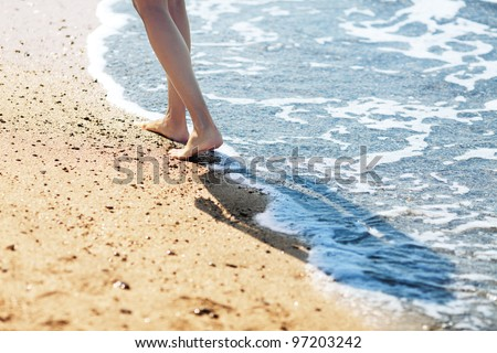 Walking barefoot along the surf on the sand beach - stock photo