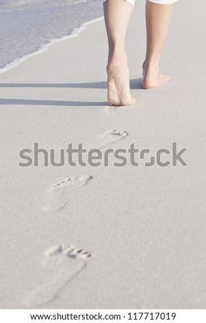 walking barefoot in the sand in summer holidays on beach - stock photo