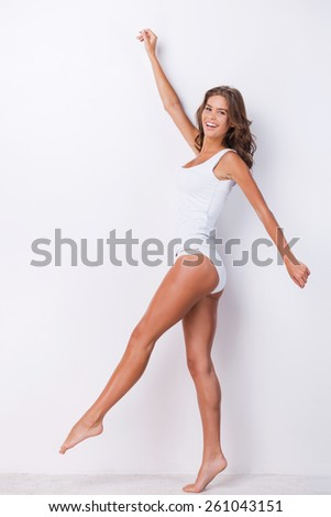 Walking beauty. Full length of attractive young brown hair woman in tank top and panties posing against white background and smiling - stock photo