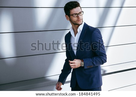 Walking business man. Elegant young handsome man wearing glasses and watchers. - stock photo