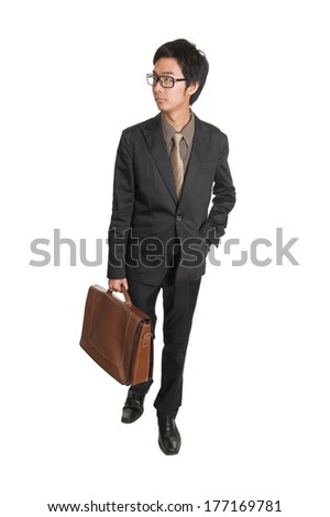 Walking business man holding a briefcase and looking to his side on white background