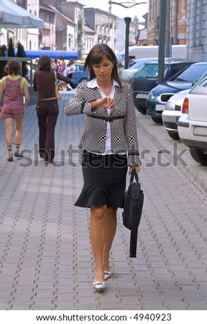 Walking businesswoman while she is checking the time - stock photo