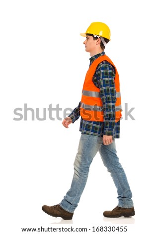 Walking construction worker in yellow helmet and orange waistcoat.  Full length studio shot isolated on white. - stock photo