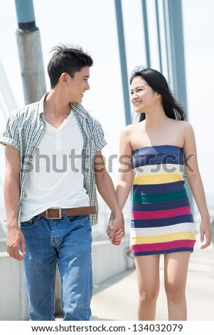 Walking couple holding each other's hands outside - stock photo