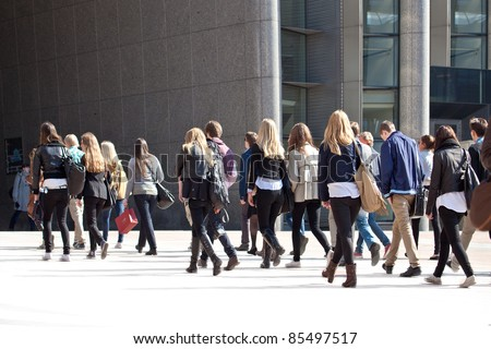 Walking Crowd. A crowd of people stroll on a sidewalk. All exposed faces are motion blurred. - stock photo