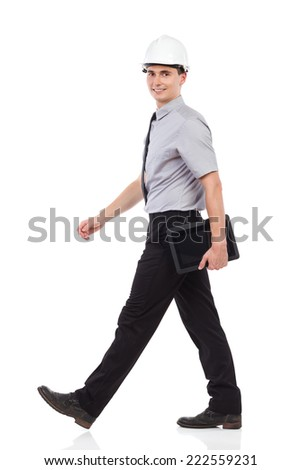 Walking engineer with a digital tablet, side view, looking at camera. Full length studio shot isolated on white. - stock photo