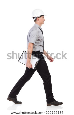 Walking engineer with clipboard, side view. Full length studio shot isolated on white. - stock photo