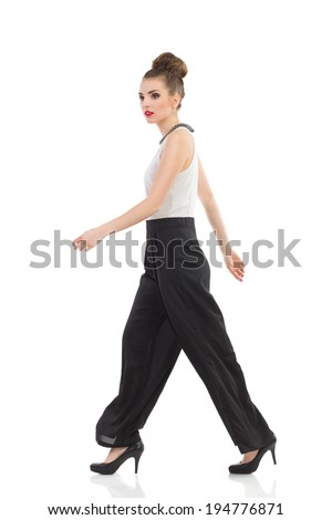 Walking fashion model. Side view. Full length studio shot isolated on white. - stock photo