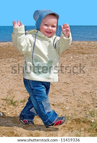 walking happy kid on the spring sea beach