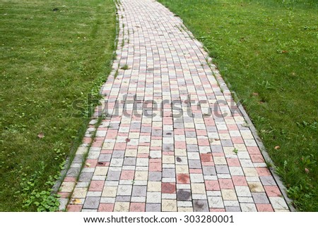 Walking lane from colored tile with green grass - stock photo