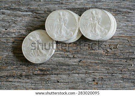 Walking liberty silver dollars stacked against weathered - aged barn wood table top - stock photo