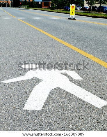 Walking Man Road Sign. Silhouette of a person walking painted on the street, a road sign marking a pedestrian crossing. - stock photo