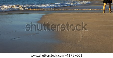 walking on a beach and leaving footprints - stock photo