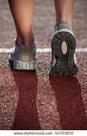 Walking on a running track. Close up of running sneakers - stock photo