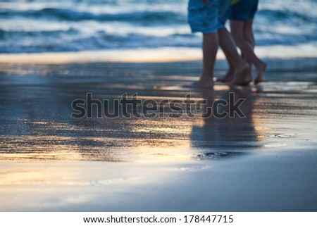 walking on the beach at sunset - stock photo