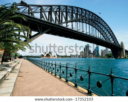 Walking on the path that leads beneath the Sydney Harbour Bridge in Australia.  Cityscape of Sydney behind. - stock photo